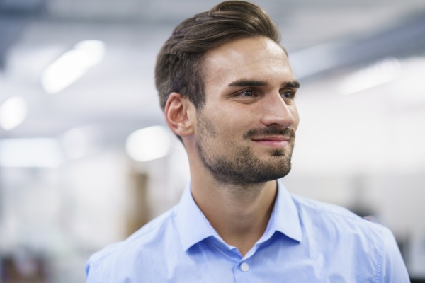 smiling young businessman looking away at
