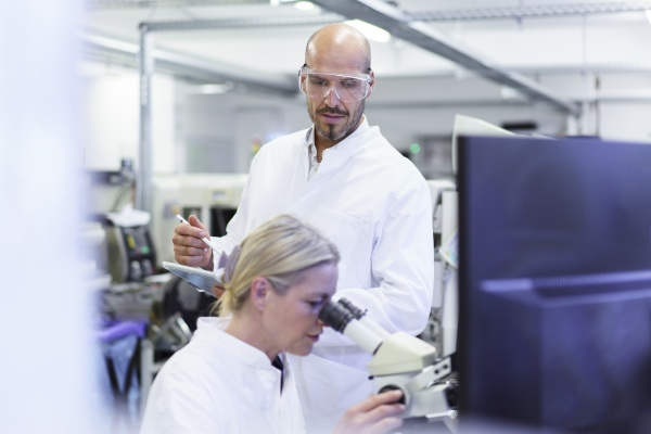 male technician looking at female scientist