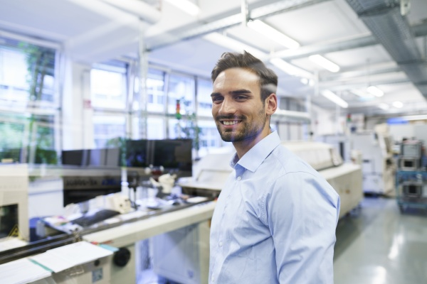smiling young male technician standing at