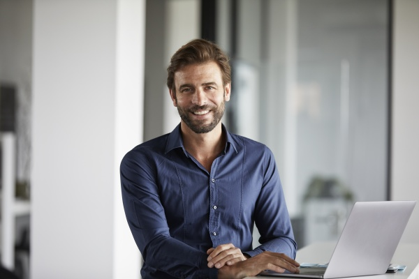 smiling businessman using laptop while standing