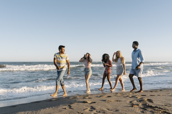 young friends walking on beach during