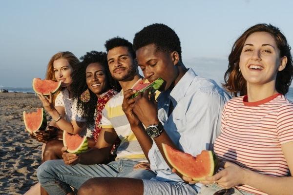friends enjoying eating slice of watermelon