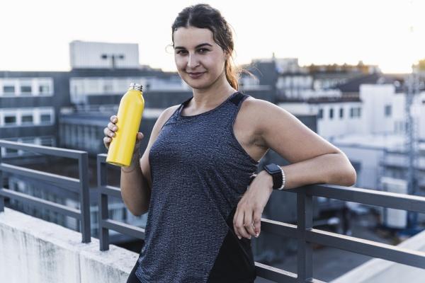 smiling female athlete holding bottle while