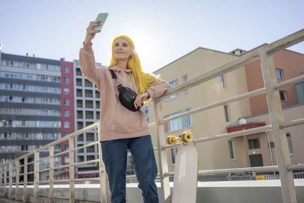 smiling young woman taking selfie on