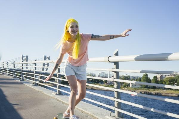 hipster female doing skating on bridge