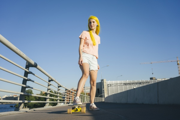 woman standing on skateboard against clear