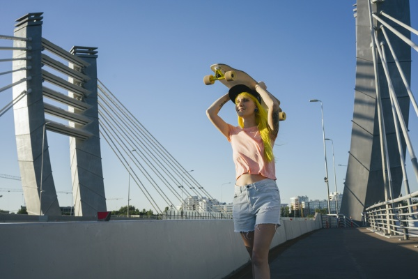 young woman lifting skateboard on head