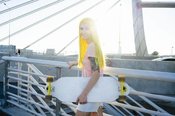 woman holding skateboard standing on bridge