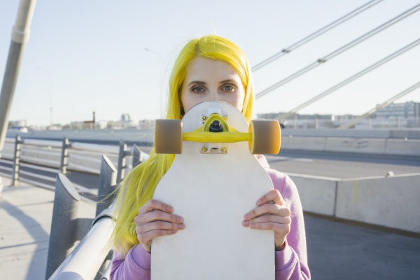 female hipster covering face with skateboard
