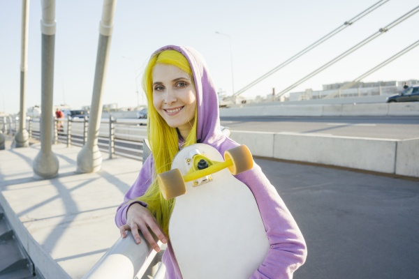 female hipster smiling while holding skateboard