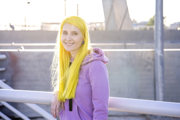 smiling hipster female standing on bridge