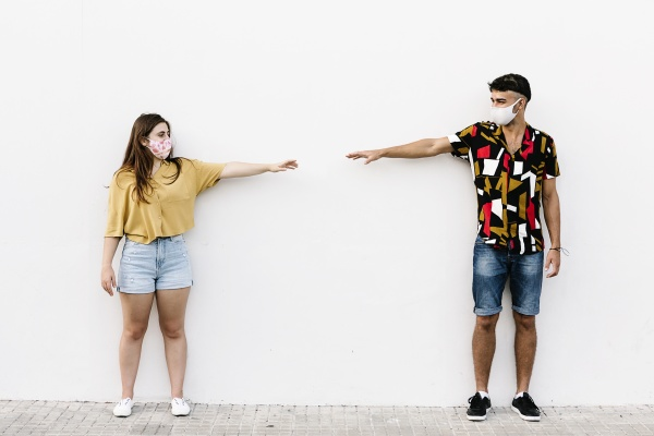 young friends keeping social distancing while