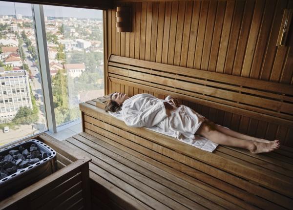 senior woman relaxing in wooden sauna
