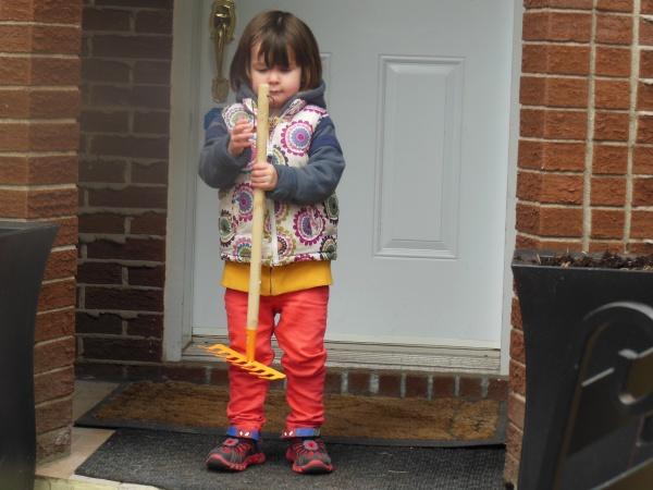 little girl with yellow rake