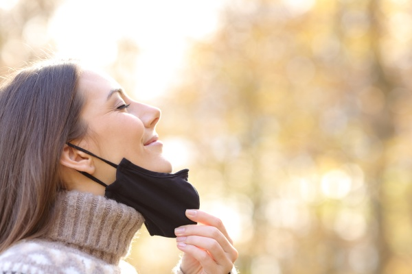satisfied woman taking off mask breathing