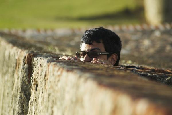 young man peeking over fence