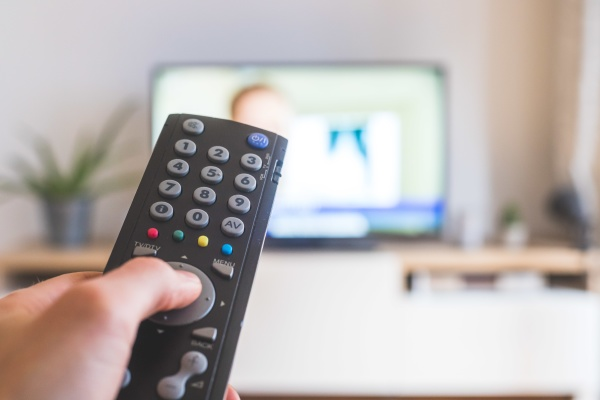 male hand is holding tv remote