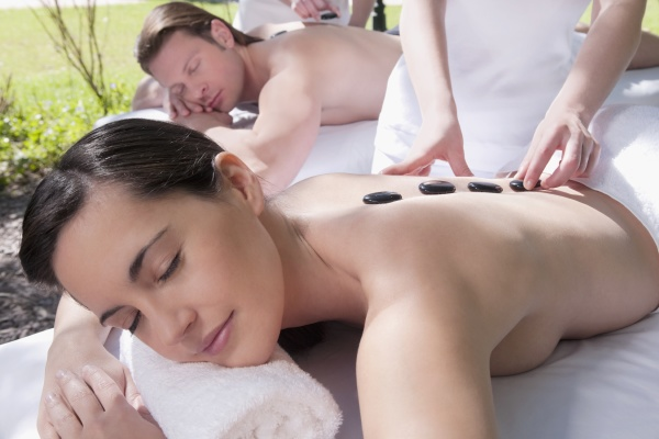 couple receiving hot stone therapy from