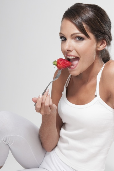 woman eating a strawberry on a