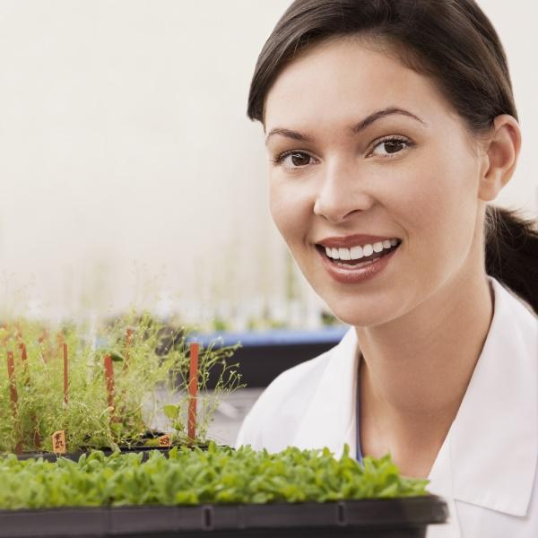 female scientist smiling near plants in