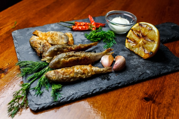 fried fish on chopping board with