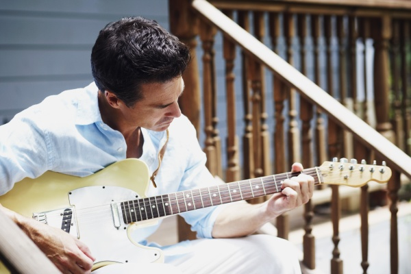 mature man playing the guitar