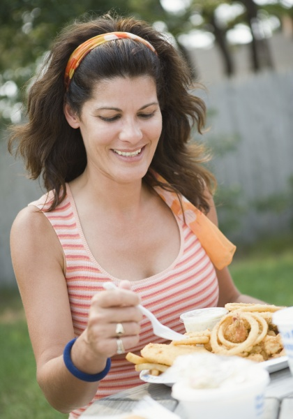 mature woman eating snacks and smiling