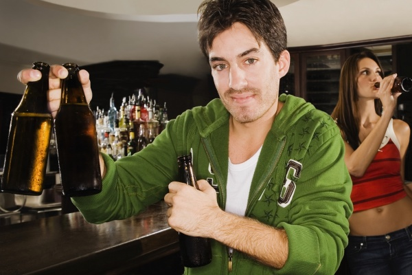 young man holding a beer bottle