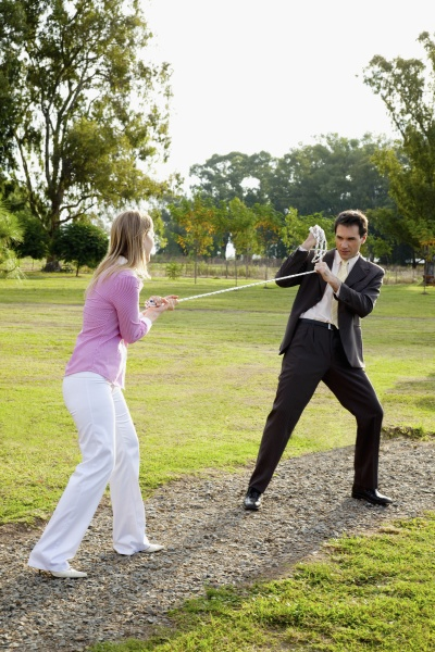 businessman and a businesswoman playing tug
