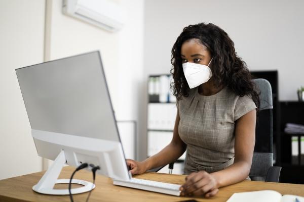 woman employee in office wearing face
