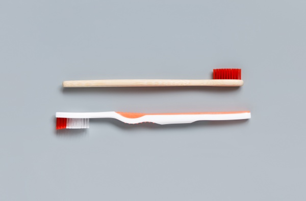 plastic and bamboo toothbrushes on grey