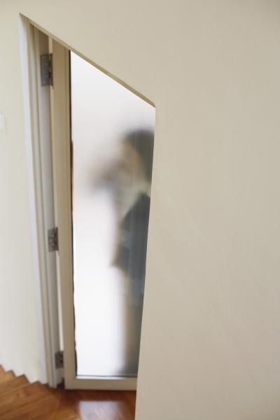 woman standing behind a door