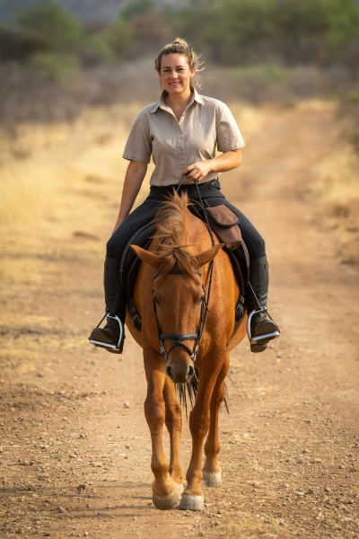 smiling blonde rides horse on dirt