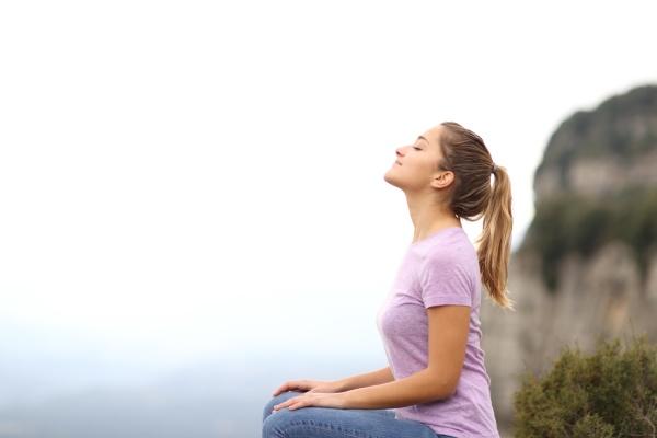 woman sitting breathing fresh air in