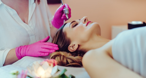 cosmetologist giving woman a skin treatment