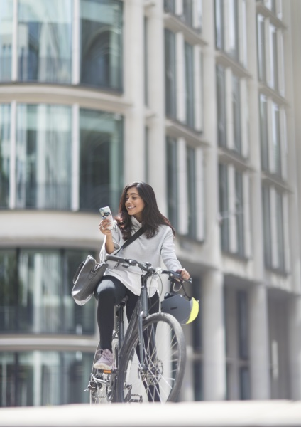 woman using smart phone on bicycle