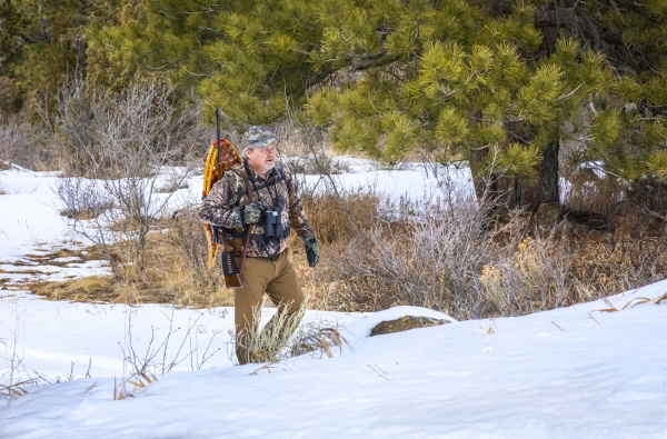 hunter with snowshoes rifle and binoculars
