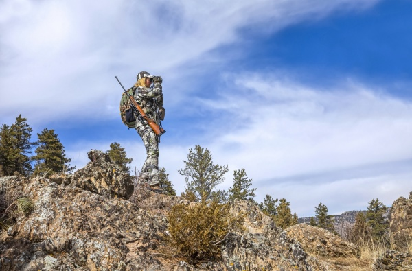 hunter with camouflage clothing and rifle