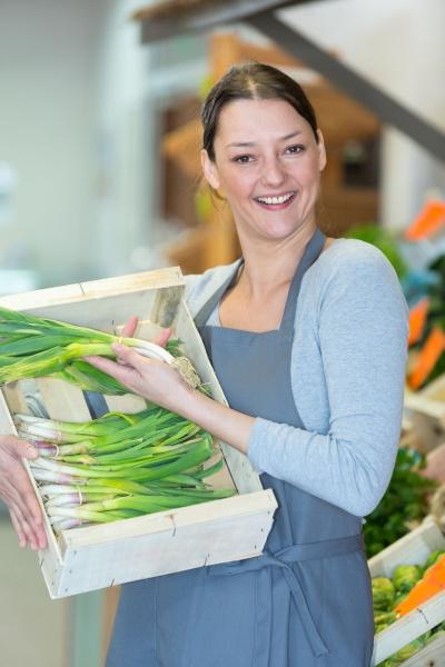 smiling female seller in vegetables market