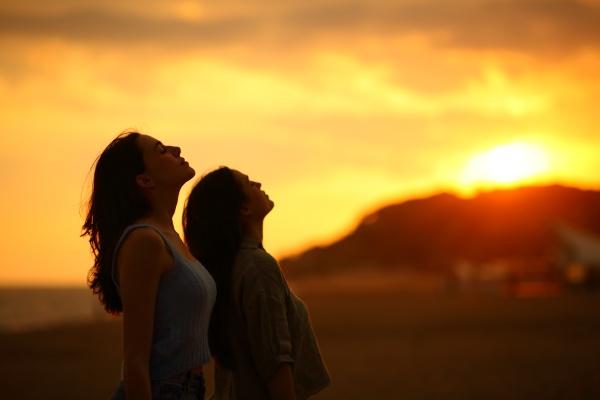 two women silhouette breathing fresh air