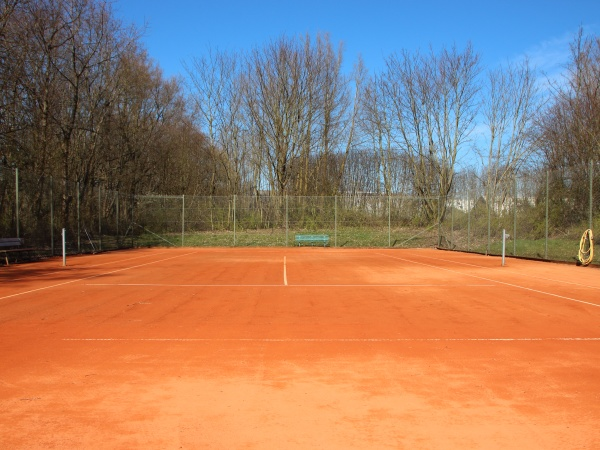 empty red clay tennis court in