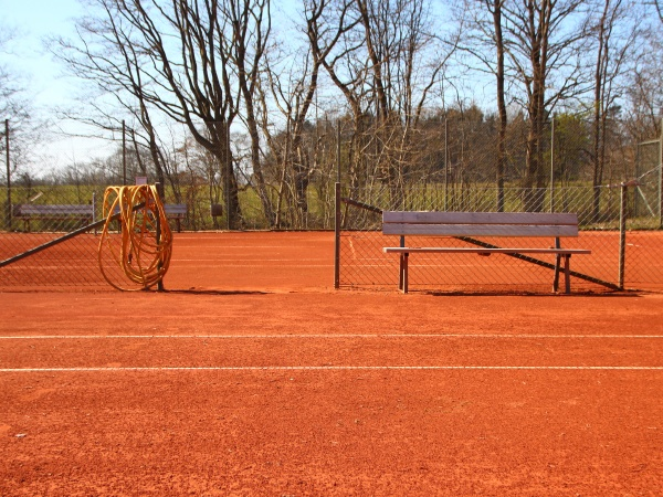 detail of empty red gravel tennis