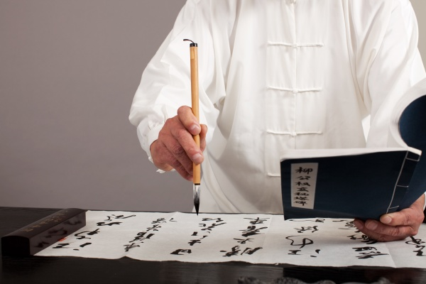 an old man practicing calligraphy