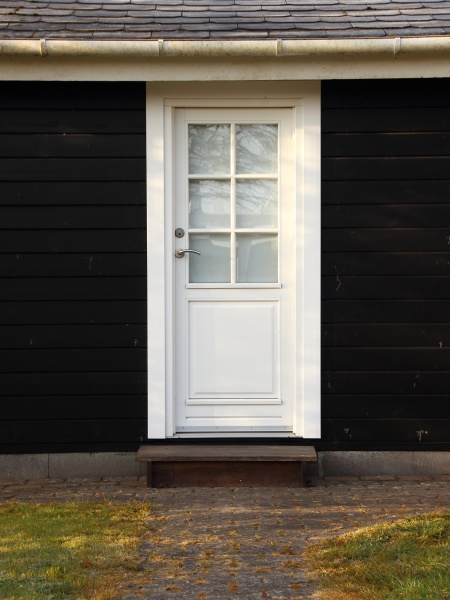 isolated white door on black wooden
