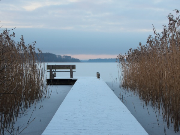snow covered pier at lake with