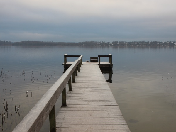 empty pier with wooden railing in