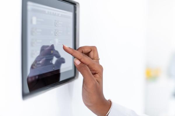 african woman using smart home screen