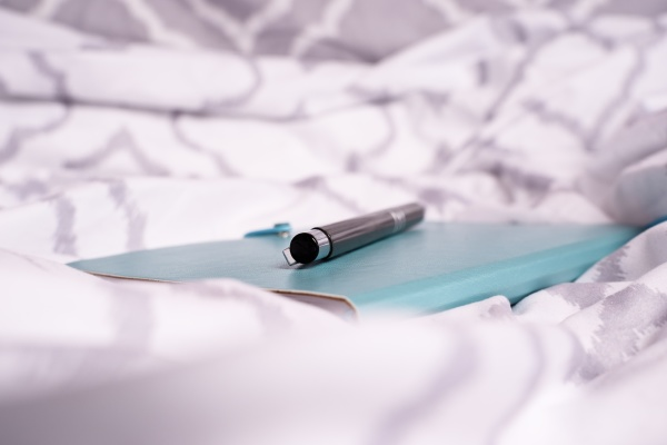 notepad and pen on bed with