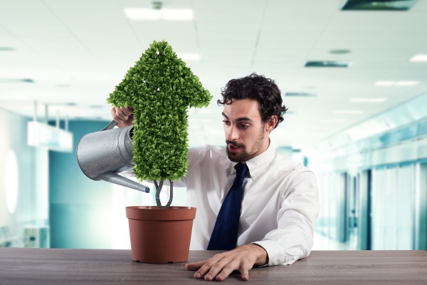 businessman that watering a plant with