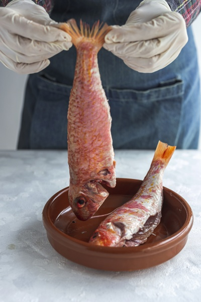 person holds raw mullus fish